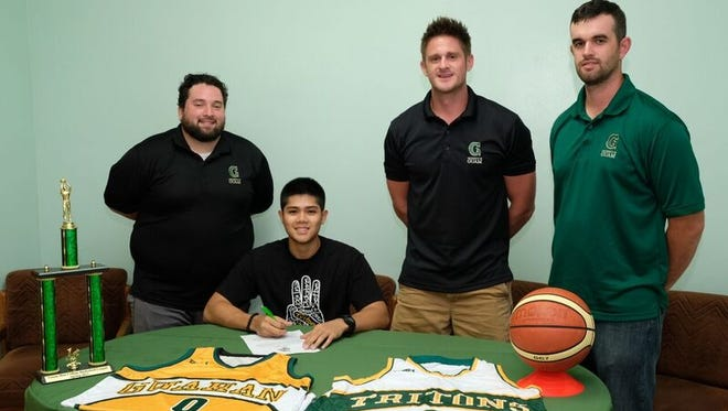 Andrew (AJ) Carlos signs his Letter of Intent and Athletic Scholarship alongside UOG Head Coach Brent Tipton with assistant coaches Josh Torres (left) and Stephen Yates (Right) to their sides.