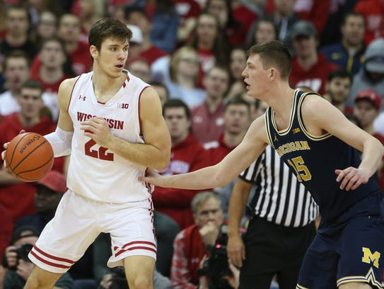 Wisconsin forward Ethan Happ battles Michigan center Jon Teske on Sunday.