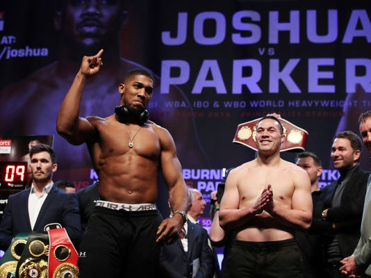 Britain's Anthony Joshua, left, and New Zealand's Joseph Parker during the weigh in, at Cardiff's Motorpoint Arena on Friday March 30, 2018, ahead of their world heavyweight unification title fight on Saturday. (Nick Potts/PA via AP)