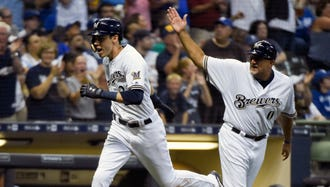 Jul 21, 2018; Milwaukee, WI, USA;  Milwaukee Brewers left fielder Christian Yelich (22) is greeted by third base coach Ed Sedar after hitting a solo home run in the sixth inning during the game against the Los Angeles Dodgers at Miller Park. Mandatory Credit: Benny Sieu-USA TODAY Sports