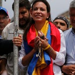 Maria Corina Machado is surrounded by colleagues during a rally in Caracas, Venezuela, Tuesday, April 1, 2014.