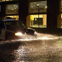 A police car makes its way on a flooded street in downtown Charleston, SC on October 03, 2015.