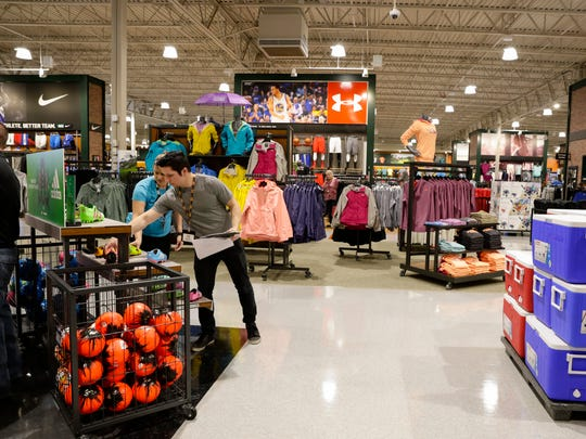 Employees arrange a shoe display at DICK'S Sporting Goods and Field and Stream stores, to open April 1, at the Ambassador Town Center in Lafayette March 22, 2016.