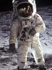 "Astronaut Edwin F. ""Buzz"" Aldrin Jr., lunar module pilot, faces the camera as he walks on the Moon during Apollo 11 extra vehicular activity in this file photograph. The plexiglass of his helmet reflects back the scene in front of him, such as the Lunar Module and Astronaut Neil Armstrong, taking his picture.  Armstrong, Apollo 11 commander, took this photograph with a 70mm lunar surface camera."