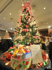 A tree lights up the room at Stoney Creek Inn in Rothschild as part of the annual Festival of Trees fundraising event for Aspirus Comfort Care and Hospice Services. Decorated holiday trees and items display Tuesday afternoon, Nov. 25, 2014, at Stoney Creek Inn in Rothschild.