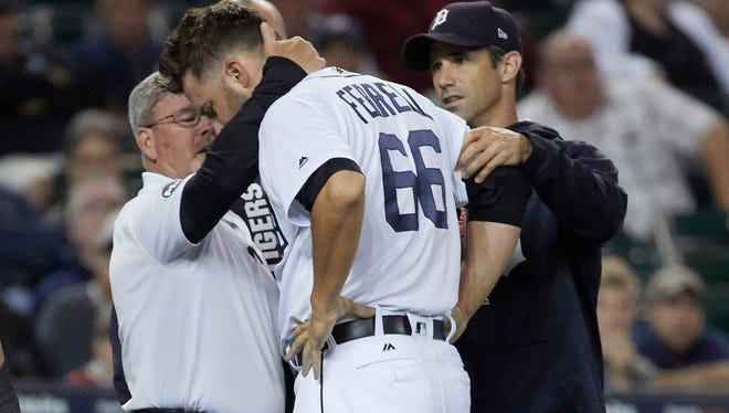 Tigers pitcher Jeff Ferrell (66) is checked by manager Brad Ausmus (right) and trainer Kevin Rand (left) after he is struck in the head by a ball hit by Athletics designated hitter Ryon Healy (not pictured) in the eighth inning of the Tigers' 8-3 loss to the A's on Monday, Sept. 18, 2017, at Comerica Park.