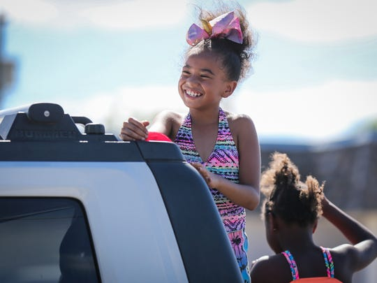 Kids smile at the crowds along the streets during the