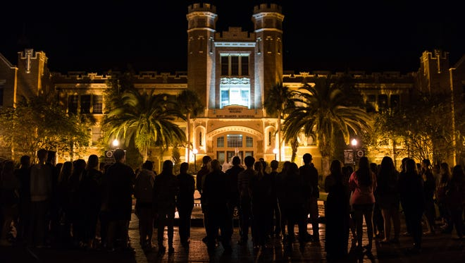 Sun., Nov. 15, 2015, Florida State University students hold a vigil at the Wescott Fountain in honor of those killed or injured in the terrorist attacks on Paris the past Friday.