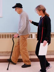 Pete Cuffe practices walking with a wide stance. Instructor Bonnie Holben makes sure Pete's balance is good.