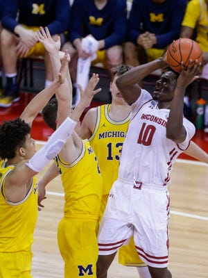 Wisconsin's Nigel Hayes (10) shoots against Michigan's D.J. Wilson, left, Duncan Robinson and Moritz Wagner (13) during the first half Tuesday in Madison, Wis.