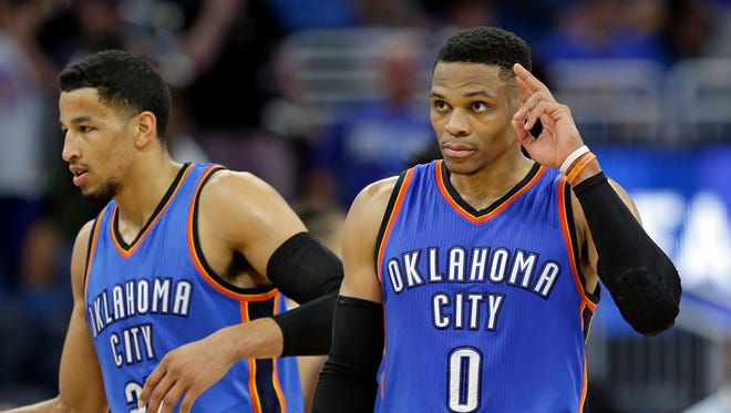 Oklahoma City Thunder's Russell Westbrook (0) salutes cheering fans as he comes off the court with teammate Andre Roberson, left, after defeating the Orlando Magic 114-106 in overtime in an NBA basketball game, Wednesday, March 29, 2017, in Orlando, Fla. Westbrook scored 57 points in the game.