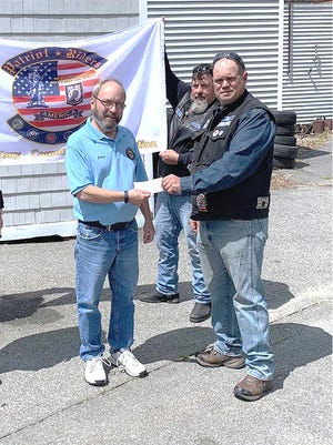 Jim Benton, president of Vietnam Veterans of America Chapter 907, left, receives a check for $1,000 from Neil Goguen, president of Patriot Riders of America Chapter 3, right, as member Jason Bourgeois holds the Patriot Riders flag.