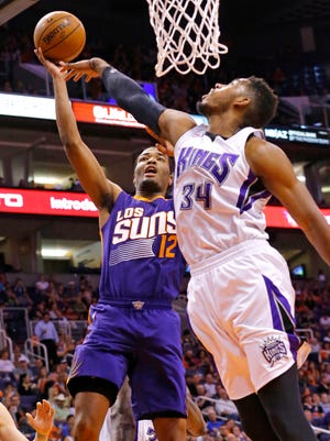 Suns forward T.J. Warren (left) shoots over Kings forward Jason Thompson during the first half of their game on Wednesday at US Airways Center in Phoenix.