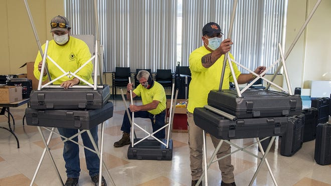 Department of Public Works and Parks workers assemble voting booths Thursday at the Worcester Senior Center  for early voting. Polls are open from 9 a.m. to 5 p.m. Saturday at the center.
