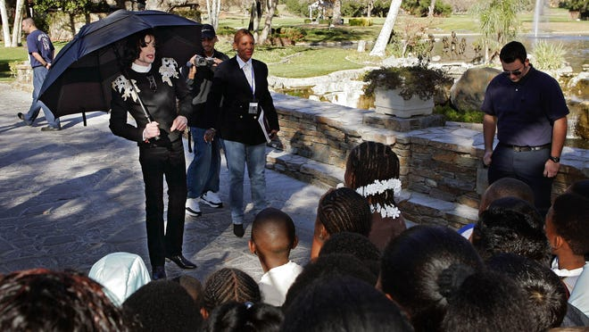 In this Dec. 17, 2004 file photo, pop star Michael Jackson greets several hundred children that were invited guests at his Neverland Ranch home in Santa Ynez, Calif.