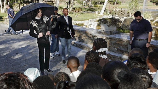 "In this Dec. 17, 2004, file photo, pop star Michael Jackson greets several hundred children who were invited guests at his Neverland Ranch home in Santa Ynez, Calif. The co-executor of Jackson's estate says he's confident the late superstar's supporters will be able to protect his legacy and brand in the wake of HBO's ""Leaving Neverland,"" a documentary detailing allegations of sexual abuse."
