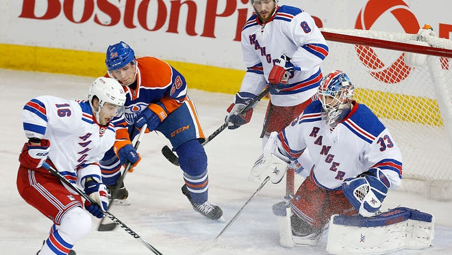 New York Rangers forward Derick Brassard (16) clears a puck from in front of goaltender Cam Talbot (33) during the second period against the Edmonton Oilers at Rexall Place.
