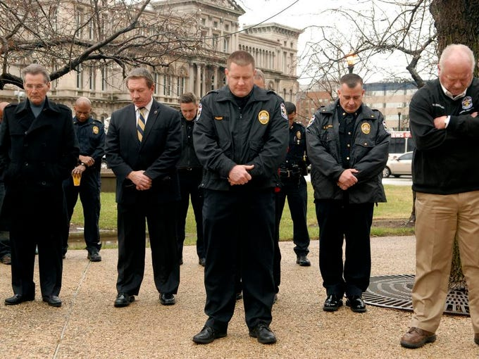 Deputy Chief Ozzy Gibson, center, bows his head in