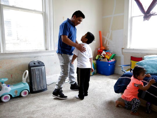 Edgar Perez Ramirez, left, stands with his 4-year-old son, Franco, in their home in Covington, Ky., on April 28, 2018. Perez left San Marcos, Guatemala, for Kentucky after his father was killed. He was heading to work when agents stopped and arrested him in December. (AP Photo/Gregory Bull)