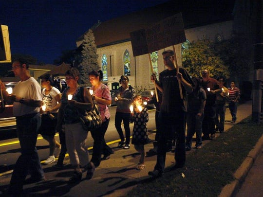 Members of San Carlos Borromeo Church hold a vigil march through the streets of Carthage in October 2011 for an undocumented Hispanic immigrant.