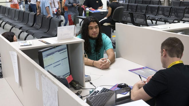 Eloy Herrera, of Phoenix, left,  is assisted by customer service representative, Daniel Szabo, at the Arizona Department of Transportation Motor Vehicle Division in Phoenix on June 16, 2016.