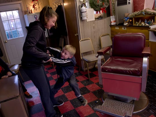 Big sister Kaylee Longenette, 12, pulls rank on little brother Aiden Aders, 6, as she removes him from the empty barber chair at Cooper's Barber Shop at 610 W. Ninth Street in Owensboro, Kentucky.