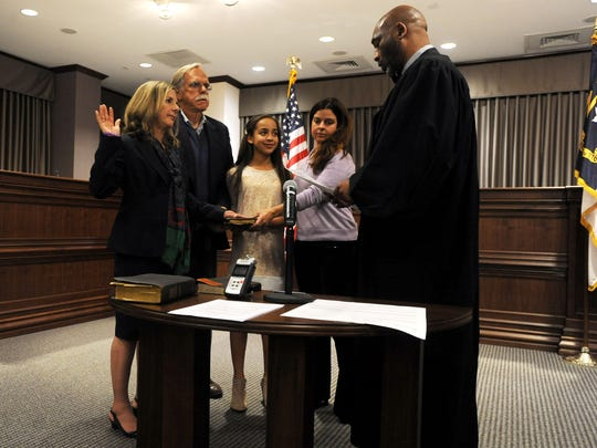 Buncombe County Commissioner Ellen Frost is sworn in for a second term Monday evening Dec. 1, 2014. With Frost is Lawernce Madens, 12-year-old Lexi All, Elizabeth Allen and Buncombe County Judge Calvin Hill. Frost took the oath of office using the Bible of the South's first elected female legislature and Black Mountain native Lillian Exum Clement Stafford.