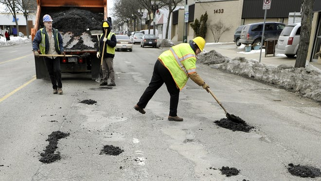 City of Lansing employees patch potholes on Michigan Avenue in 2011.  The Lansing Regional Chamber of Commerce is asking the city to fix road to accommodate all the new development along the corridor.