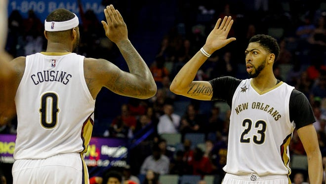 New Orleans Pelicans forward Anthony Davis (23) high fives forward DeMarcus Cousins (0) during the second half of a game against the Memphis Grizzlies at the Smoothie King Center.