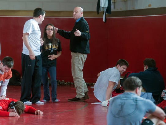 In 2014, David Bell chats with students as wrestlers