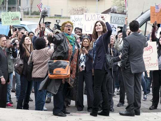 "Actress-singer Jill Scott, left center, and Betsy Brandt, right center, play two of the women protesting the toxic water in Flint in Lifetime's drama ""Flint,"" which premieres Saturday."