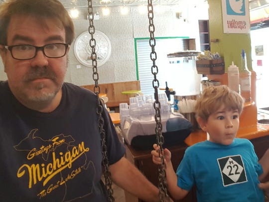 Writer Eric Spitznagel and his son wear their Michigan gear in a Chicago ice cream shop. Spitznagel, a Michigan native, is considering a memoir about Michigan.
