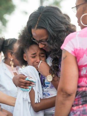 Tiy'uana Vason, 10, and her aunt Shantara Hurry comfort each other  during a candlelight vigil for Shantara's daughter Naomi Jones held at Olive Baptist Church in Pensacola on Thursday, June 8, 2017.