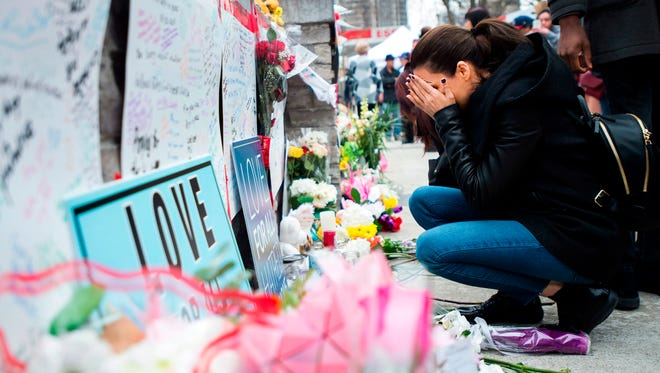 A women fights back tears at a memorial along Yonge Street on April 24, 2018, in Toronto, the day after a driver drove a van down sidewalks, striking and killing numerous pedestrians in his path.