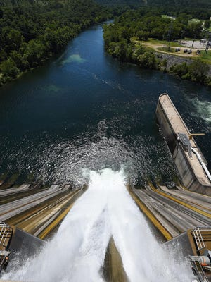 At about 200 cubic feet per second, water in the 80-degree temperature range rushes from a tainter gate leak at the Norfork Dam on Friday. The impact of fluctuating water temperatures on trout in the North Fork River has local conservationists and anglers worried.