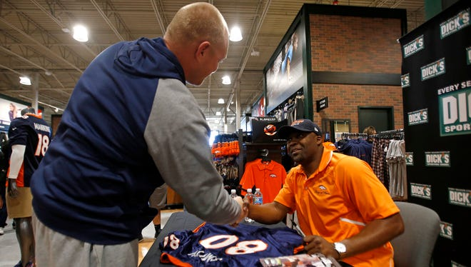 Travis Perkins, left, of Farmington, shakes hands with former Denver Broncos wide receiver Rod Smith on Saturday at the new Dick's Sporting Goods on East Main Street in Farmington.