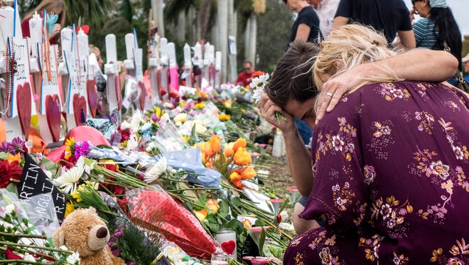 People visit a makeshift memorial in front of the Marjory Stoneman Douglas High School in, Parkland, Fla. on Feb. 20,  2018.