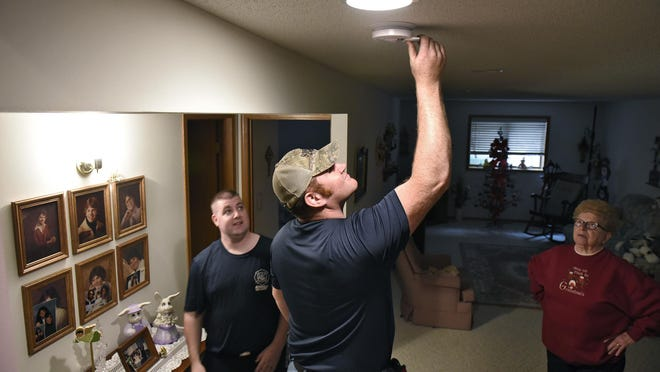 Firefighters Chris Weber, left, and Josh Kneip check the batteries in a fire detector in the home of Dorothy Porwoll last year in Rockville.