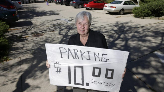 Sally Maddick of Central United Methodist Church holds a parking sign used at the church parking lot for events at the nearby Rave.
