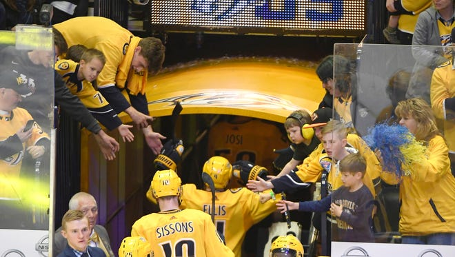 Fans reach out to the Predators after the team's 5-4 win over the Avalanche in game 2 of the first round NHL Stanley Cup Playoffs at Bridgestone Arena Saturday, April 14, 2018, in Nashville, Tenn.