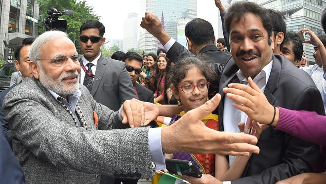 Indian Prime Minister Narendra Modi, left, is greeted by Indian residents in South Korea as he visits the Cheonggye stream in Seoul on May 19, 2015.