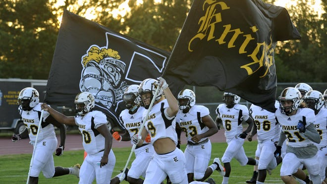 The Evans High School football team runs onto the field ahead of a game on Friday, Sept. 4, 2020 at Cross Creek High School.