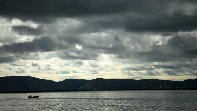 """A lone fisherman continues to work under cloudy skies on Lake Titicaca near the city of Puno, Peru. Officials are worried about the lake's water levels. """"If global warming continues ... lake levels will go down,"""" said Bolivian Mountain Institute Director Dirk Hoffmann."""