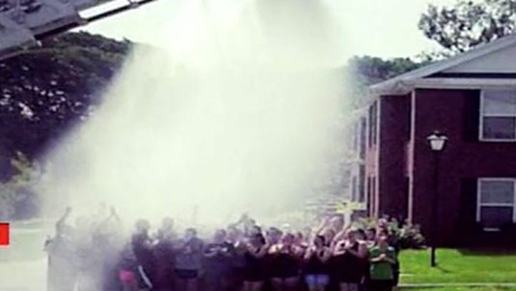 Campbellsville firefighters spray Campbellsville University's marching band with water as they assisted in an ALS ice bucket challenge. Firefighters were injured not long after when the aerial came in contact with power lines.