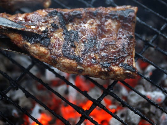Spareribs are turned with a gripper on a charcoal barbecue
