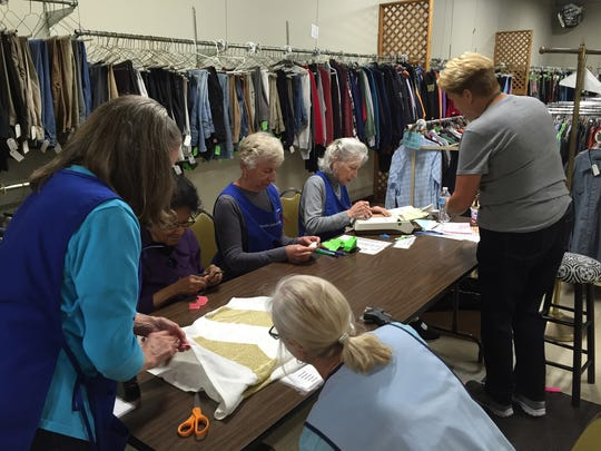 The Ladies of Charity volunteers work hard getting donated and consigned items ready for their annual sales. The organization also gives away clothing to the needy in the community.