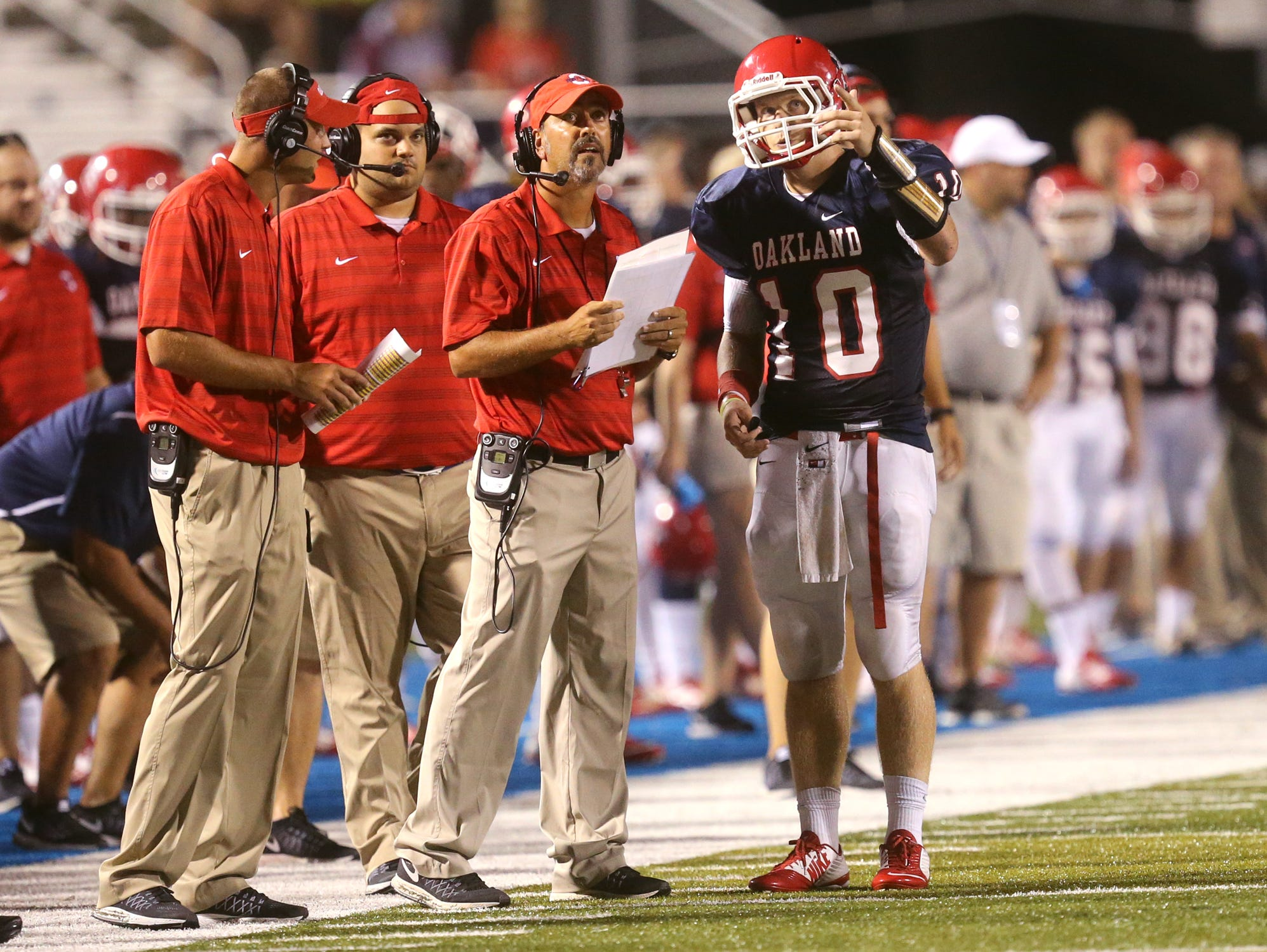 Oakland's quarterback Brendon Matthews (10), talks with the head coach Kevin Creasy during the game against Hoover at the Middle Tennessee Classic at MTSU's Floyd Stadium, on Saturday, Aug. 22, 2015.
