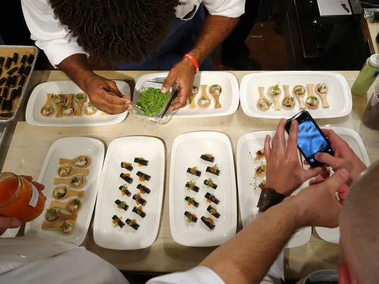 The chefs start plating hors d'oeuvres as the first
