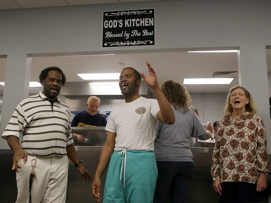 Michael Brown, center, leads those gathered at the Regional Inter-Faith Association Soup Kitchen in song on Thursday.