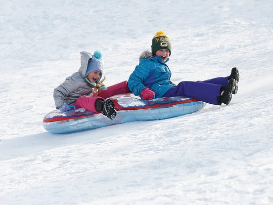 Kids take advantage of the recent snowfall to sled down Buttermilk Creek Park hill.
